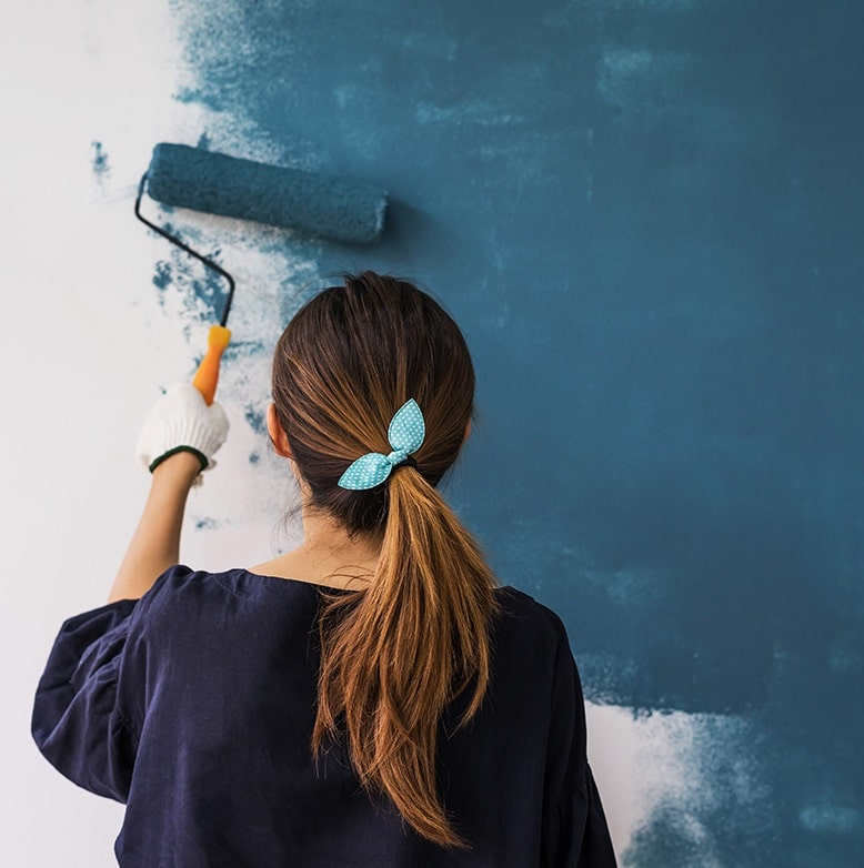 Une femme fait de la peinture sur un mur - Les couleurs tendances de 2022 s'invitent déjà chez vous
